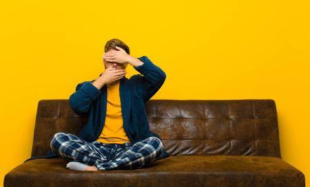 young man wearing pajamas covering face with both hands saying no to the camera! refusing pictures or forbidding photos . sitting on a sofa