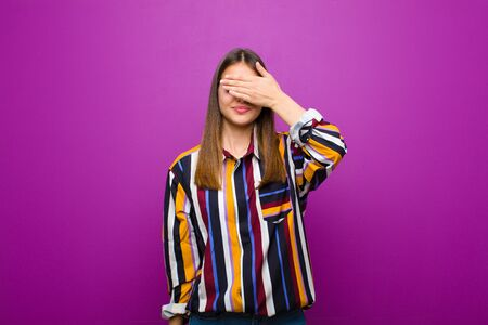 young pretty woman covering eyes with one hand feeling scared or anxious, wondering or blindly waiting for a surprise against purple background Standard-Bild - 135947586