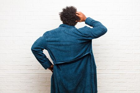 young black man wearing pajamas with gown feeling clueless and confused, thinking a solution, with hand on hip and other on head, rear view against brick wall
