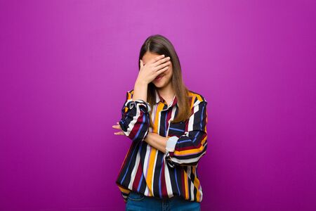young pretty woman looking stressed, ashamed or upset, with a headache, covering face with hand against purple background Standard-Bild - 135947820