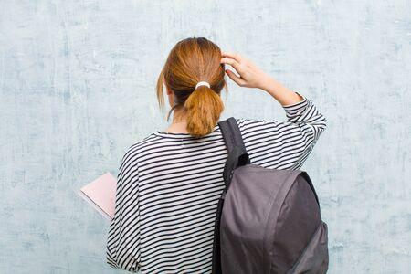 junge Studentin, die sich ahnungslos und verwirrt fühlt und eine Lösung denkt, mit der Hand auf der Hüfte und der anderen auf dem Kopf, Rückansicht gegen Grunge-Wandhintergrund