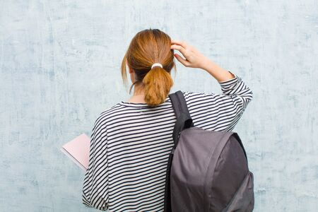 young student woman feeling clueless and confused, thinking a solution, with hand on hip and other on head, rear view against grunge wall background Standard-Bild - 135947258