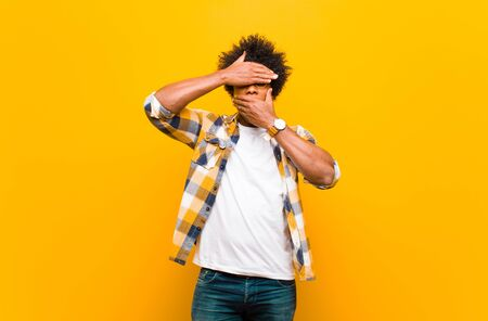 young black man covering face with both hands saying no to the camera! refusing pictures or forbidding photos against orange wall Standard-Bild - 135947981