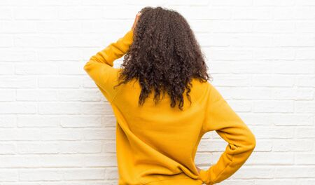 young black woman feeling clueless and confused, thinking a solution, with hand on hip and other on head, rear view against brick wall Standard-Bild - 135963297