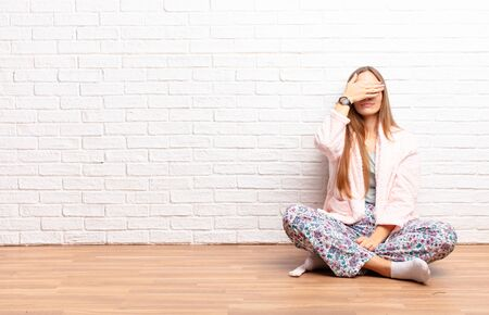 young pretty woman covering eyes with one hand feeling scared or anxious, wondering or blindly waiting for a surprise . home concept Standard-Bild - 135963199
