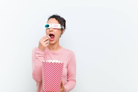 young pretty woman with pop corns and 3d glasses against white wall Standard-Bild