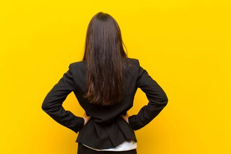 young  pretty woman feeling confused or full or doubts and questions, wondering, with hands on hips, rear view against orange wall Standard-Bild - 135963644