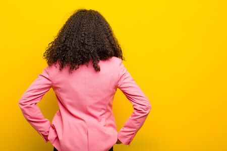 black business woman feeling confused or full or doubts and questions, wondering, with hands on hips, rear view against orange wall Standard-Bild - 135963504