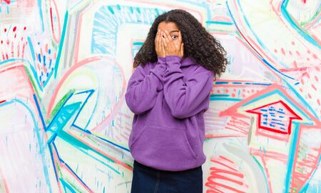 young pretty african american woman feeling scared or embarrassed, peeking or spying with eyes half-covered with hands against graffiti wall