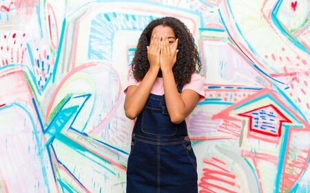 young pretty african american woman covering face with hands, peeking between fingers with surprised expression and looking to the side against graffiti wall