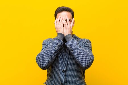 young handsome man covering face with hands, peeking between fingers with surprised expression and looking to the side against orange wall Standard-Bild - 135963966