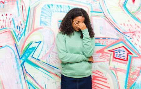 young pretty african american woman feeling stressed, unhappy and frustrated, touching forehead and suffering migraine of severe headache against graffiti wall Standard-Bild - 135964135