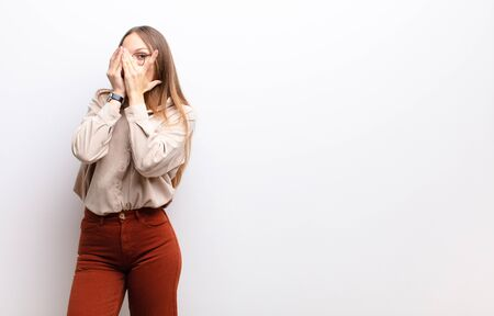 young pretty woman covering face with hands, peeking between fingers with surprised expression and looking to the side against white wall