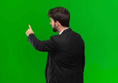 young businessman standing and pointing to object on copy space, rear view against green background Standard-Bild - 136185086