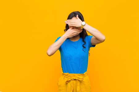 young pretty latin woman covering face with both hands saying no to the camera! refusing pictures or forbidding photos against orange wall Standard-Bild - 136185185