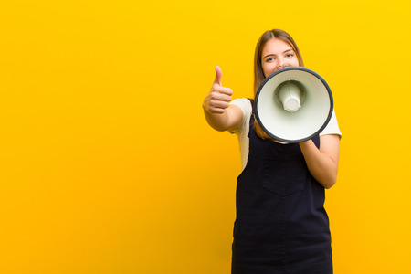 young pretty woman  with a megaphone against orange background Standard-Bild - 136409474