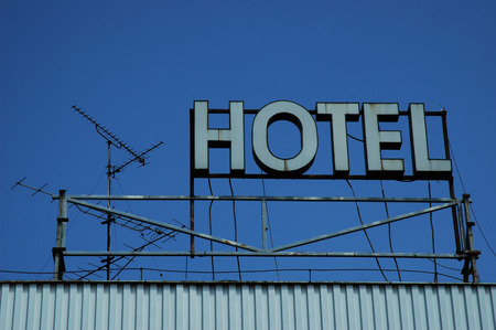 blue neon hotel sign against the blue sky photo