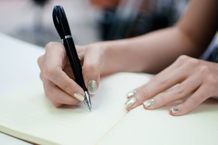 female hands with pen writing on notebook Banco de Imagens - 138284144