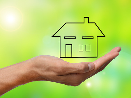 hand holding a home on green blur background Stock Photo
