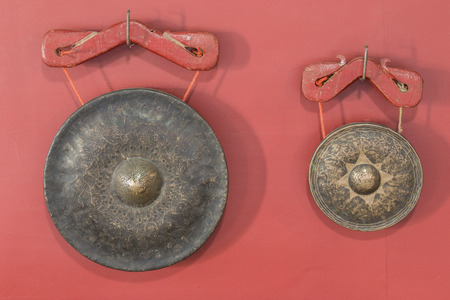 Antique brass gongstwo sizes on red background. photo