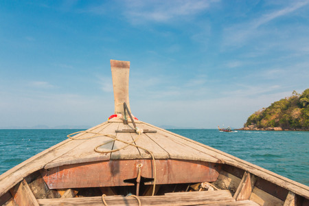 Traditional Thai wooden longtail boat heads out into the Andaman Sea on a day trip.