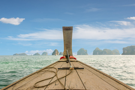 andaman sea: Traditional Thai wooden longtail boat heads out into the Andaman Sea on a day trip.