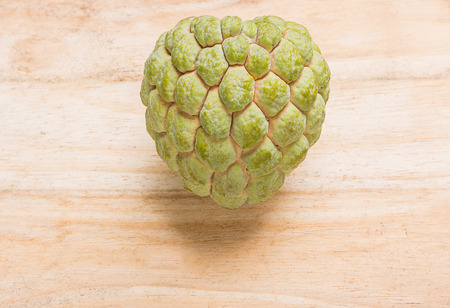 closely: Green custard apple species closely on the wooden floor.