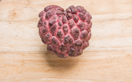 species: Red custard apple species closely on the wooden floor.
