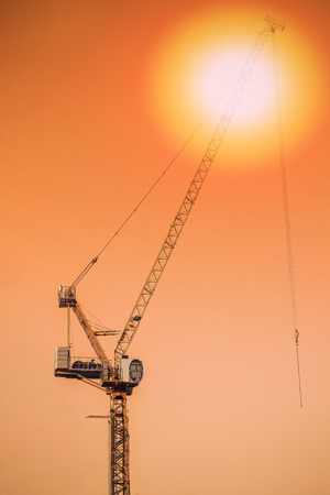 Industrial construction cranes and building silhouettes sun at sunrise.