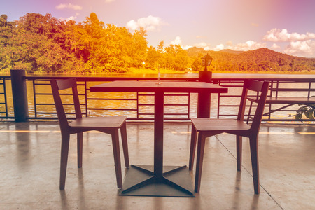 Dining table beside a lake in fall sunset.