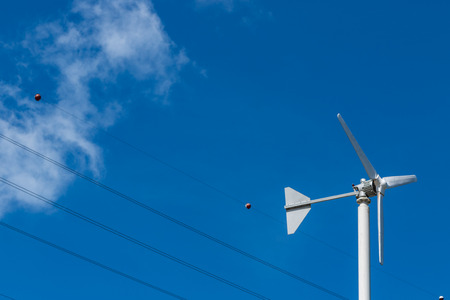 low angle view of wind turbine against partly cloudy blue sky Stock Photo