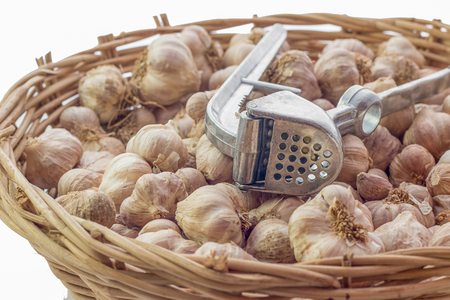 Grind garlic on wooden baskets isolated.