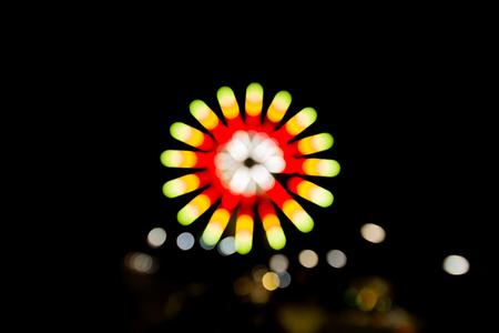Very blurred Ferris wheel at night.