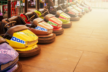 Old Bumper cars lined up at the starting line whit sunset.