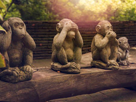 three monkeys statues which have different posts. Stock Photo