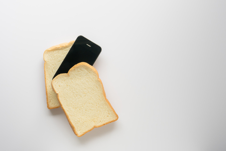 concept eat bread with a smartphone on white background. Imagens