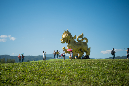 CHIANG RAI, THAILAND December 22, 2018 :Singha statue at Singha Park, Chiang Rai, Thailand. Tourists are taking pictures Gold Lion statue in Boon Rawd farm.