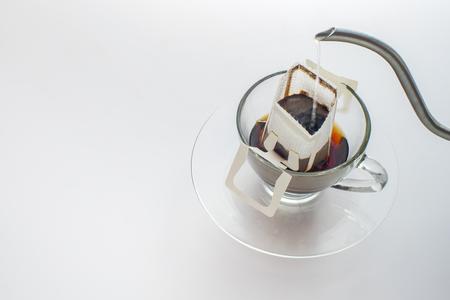 Fare il caffè con la bustina di caffè gocciolante su sfondo bianco Archivio Fotografico