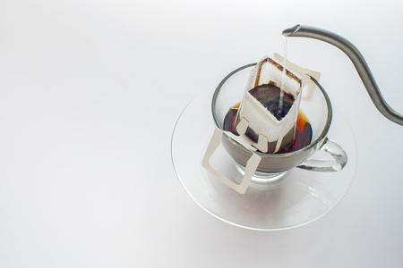 Making coffee with drip coffee bag on white background 免版税图像
