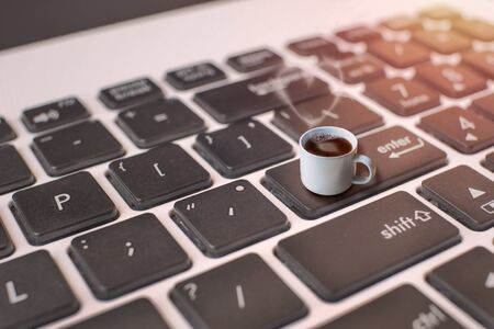 concept closeup small coffee cup on the Enter button. on keyboard.