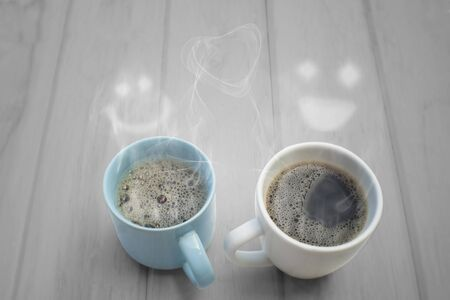 Two hot coffee and steam smiling faces on wood table.