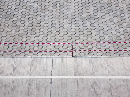 brick concrete road and lines of barrier tape