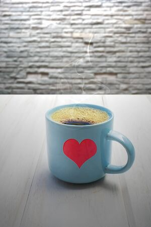 Red heart on a blue coffee mug on a white wooden table Stock fotó