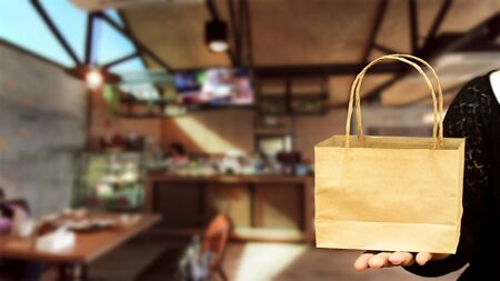 Hand holding paper bag with on coffee shop blured background Stock fotó