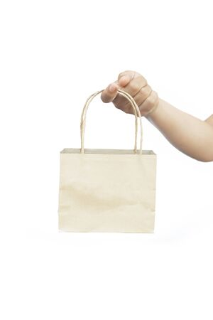 holds in hand recycled blank kraft paper shopping bag for purchases with handles on white isolated background