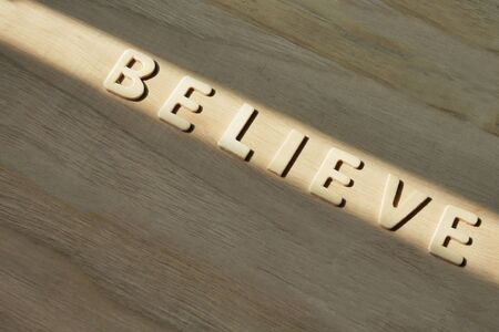 concept closeup text believe on wood.