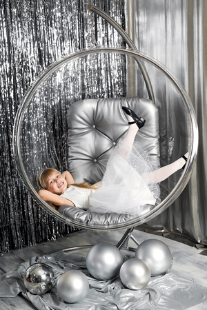 smiling girl in a transparent ball with silver christmas balls