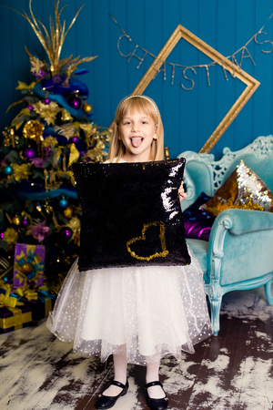 decorating: smiling girl with a pillow against the Christmas tree background