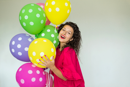 Beautiful cute cheerful girl with colored balloons. Holiday Happy Birthday Banco de Imagens