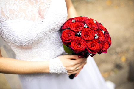 Bride in white wedding dress is holding a bouquet of red roses in hand